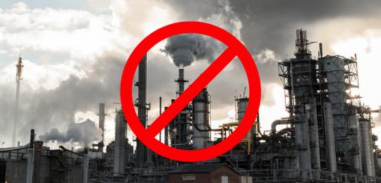 Bild einer Erdölraffinerie, aus deren Schornsteinen viel Rauch kommt. Davor ein rotes Verbotsschild